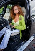 Beautiful middle-aged redhead woman with laptop behind steering wheel