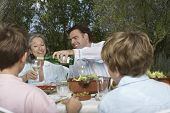 Family with children dining in garden as man pours wine into glass