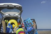 Young boy unloading air mattress from car full of beach accessories
