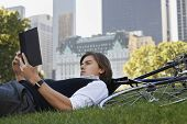 Side view of young businessman lying down on bicycle while reading book in park