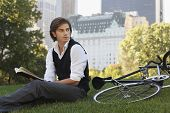 Handsome young businessman with book sitting by bicycle in park