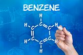 hand with pen drawing the chemical formula of benzene