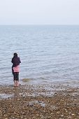 stock photo of herne bay beach  - Rear view of young woman wrapped in blanket standing by seaside on beach - JPG