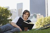 Portrait of handsome young businessman reading book in park