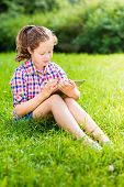 Outdoor Portrait Of A Pretty Teenager Girl In Casual Clothes Sitting On The Grass With Digital Table