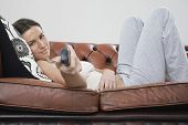 Portrait of beautiful young woman using remote control while lying on sofa at home