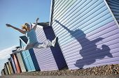 image of herne bay beach  - Active young woman jumping in front of beach huts - JPG