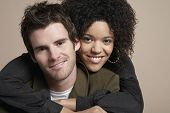 Closeup portrait of loving young couple smiling on colored background