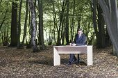 Businessman working at desk in middle of forest
