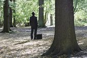 Rear view of businessman with briefcase standing in middle of forest