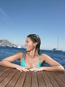 Happy young woman looking away while leaning on yacht's floorboard in sea