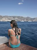 Rear view of sensuous wet woman in swimsuit sitting on yacht's floorboard
