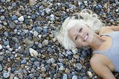 High angle portrait of beautiful young woman lying on pebbles at beach