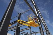 foto of cherry-picker  - Welder working from cherry picker on steel framing structure - JPG