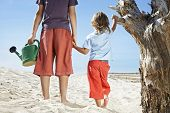 Rear view of two boys with watering can standing by dead tree on beach