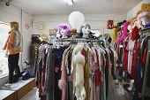 Vista de la ropa y las pelucas en una tienda abarrotada segunda mano