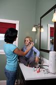Teenage Girl Applying Makeup To Young Girl In The Bathroom