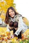 Autumn woman playing with colorful fall leaves in city park smiling happy and excited. Stylish moder
