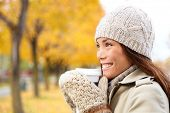 Coffee drinking woman in Autumn fall enjoying fall and hot drink from disposable cup. Smiling happy