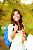 Asian student girl back to school university. Beautiful woman holding books in autumn background. Asian student girl on university college campus park smiling happy. Mixed race Asian Caucasian girl.