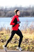 stock photo of outerwear  - Running man jogging in autumn outdoor on cold day wearing long tights and sporty jogging outfit - JPG