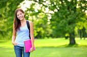 Student girl portrait holding books wearing backpack outdoor in park smiling happy going back to sch