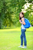 Student girl portrait wearing backpack outdoor in park smiling happy going back to school. Asian fem