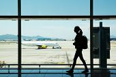 Silhouette of young Woman walking am Flughafen