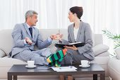 Funny businessman wearing stripey socks and talking with his colleague sitting on sofa