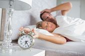 Tired couple looking at alarm clock in the morning with woman turning it off at home in bedroom