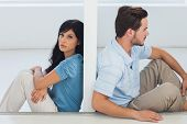 stock photo of divider  - Sitting couple are separated by wall with woman looking at camera - JPG