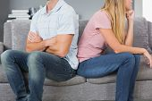 Couple sitting back to back after a fight on the sofa in sitting room at home