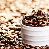 White Coffee Cup With Roasted Coffee Beans On Heap Of Coffee Beans Background. Coffee Background Tex