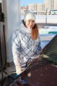 Woman Refueling Car With Petroleum At Winter Season