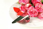 romantic table setting with roses for the holiday St. Valentine