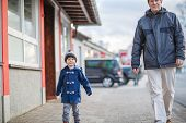 Father And  Little Son Walking On The Street In German Village