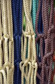 stock photo of macrame  - Colorful braided macarame hanging plant holders on display - JPG