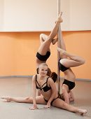 Cute young pole dancers posing with pylon