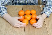 hands of a boy with oranges