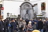 Brussels, Belgium - Fevrier 2:  Tourists Crowned In The Place Of The Manneken Pis Statue In Brussels