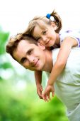picture of father daughter  - Father Giving Daughter Piggyback Ride Outdoors - JPG