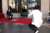 Kenny 'Babyface' Edmonds and Usher taking his photo at the Kenny