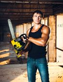 image of man chainsaw  - Muscular man with a chainsaw on the ruins - JPG