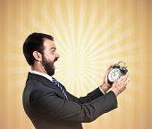 Young Businessman Holding An Antique Clock Over Ocher Background