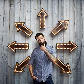 Thoughtful bearded man and lighting arrows on a wall