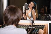 image of recording studio  - Young female singer with studio technician in foreground at the recording studio - JPG