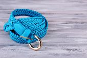 Blue leather belt on wooden background