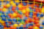 Yellow Net And Many Colored Toy Balls In Children Playground. Focus On Net
