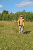 Little Beautiful Girl Overspreads Sawdust At Grass Of Green Meadow In Sunny Day