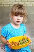 Little girl in blue dress holding bowl with hazelnuts